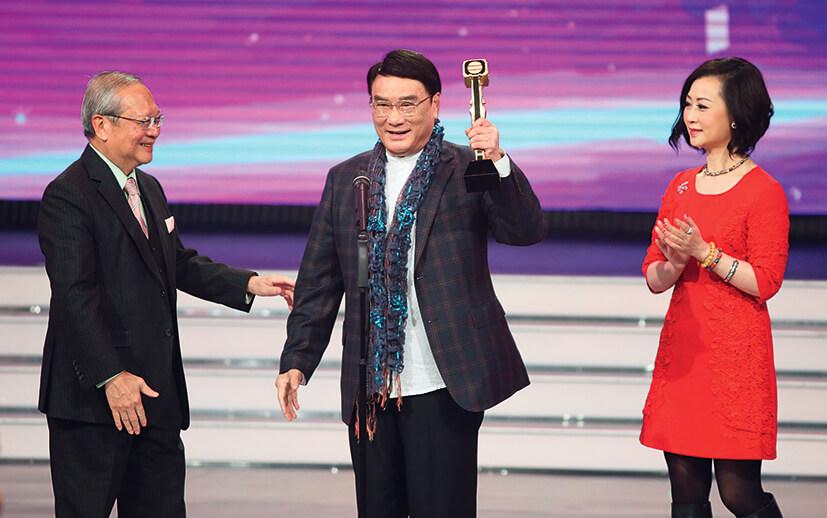 在《萬千星輝頒獎典禮2014》中,由無綫行政主席梁乃鵬頒發「萬千光輝演藝人大獎」,炳哥在女兒陪同下領獎。