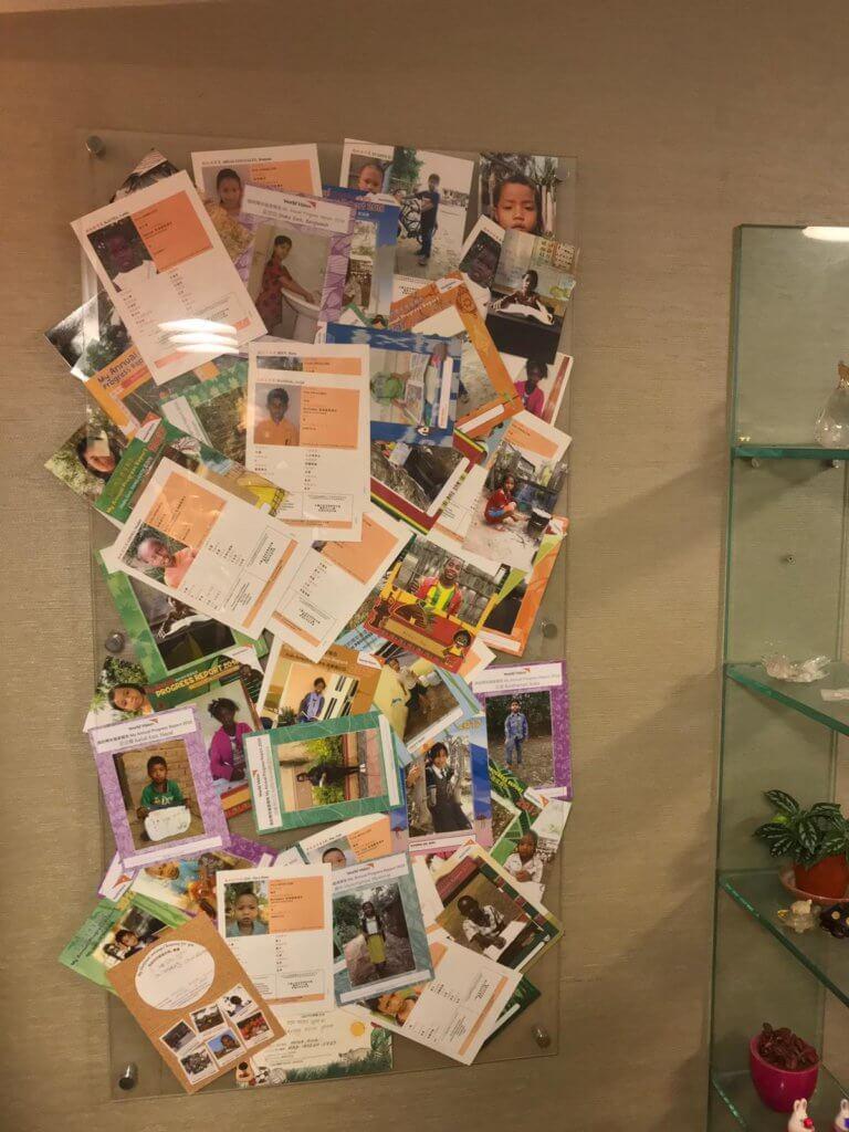 艾威多年來助養了近三十名貧困兒童,他將這些助養子女寄來的相片及畫都掛在客廳一角。