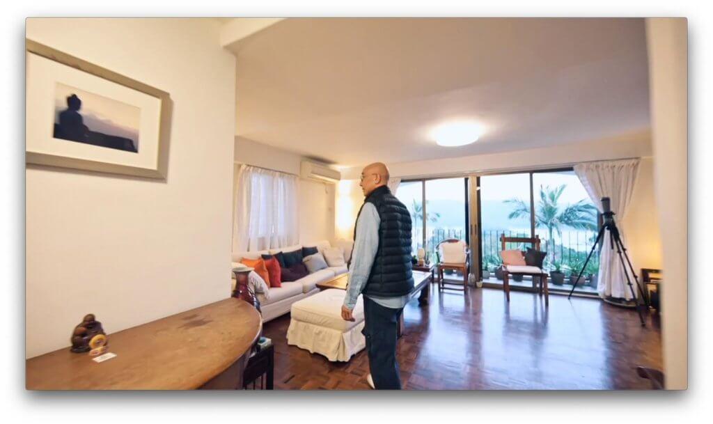 盧冠廷家中的起居室光潔明亮,落地玻璃外可看到一片翠綠的景色。