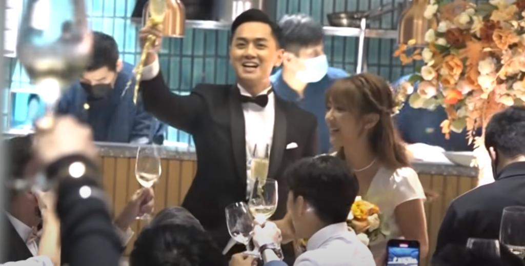 一對新人拿起香檳杯,跟場內親友祝酒,氣氛十分高漲。(娛樂新聞台截圖)