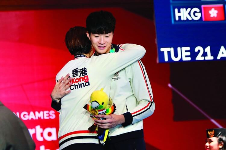 張家朗與隊友崔浩然在亞運會分奪銅牌和銀牌,獲獎後兩人相擁互賀。