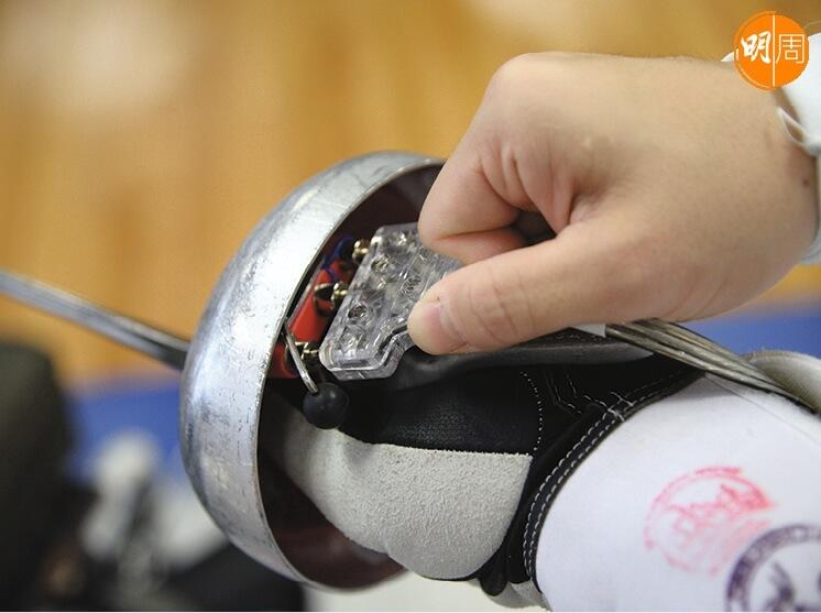 把電線穿過衣服再接駁劍柄的護手盤上,通電後刺中對手金屬衣時,裁判燈便會亮起,顯示得分。