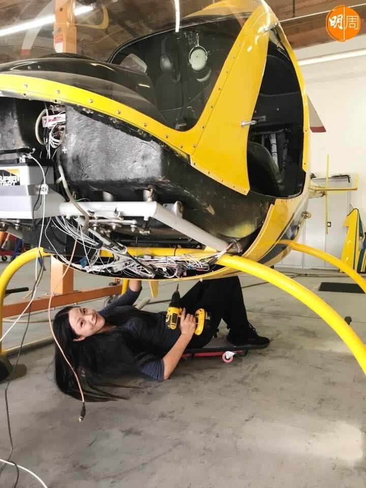 李龍基太太Chris是飛機工程師,躺在地上修理直升機。