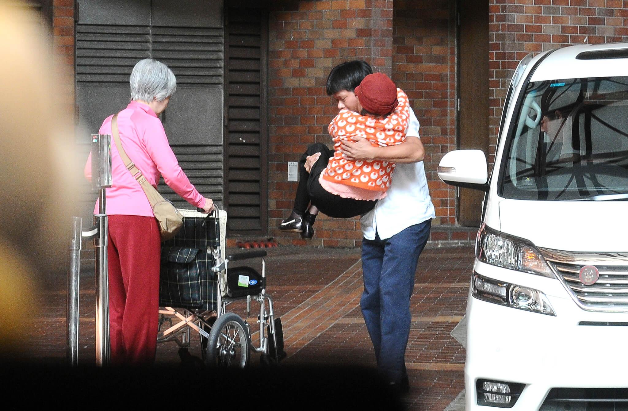 李香琴在女兒陪伴下到治療中心,記者見琴姐的女兒先落車準備輪椅,司機則抱着琴姐落車坐輪椅,同行還有私人看護。